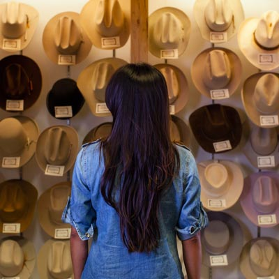 woman looking at vintage cowboy hats